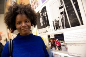 Black woman with natural fro and navy blue sweater poses along artwork in gallery space