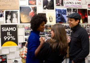 Two women and man converse in gallery space while viewing artworks