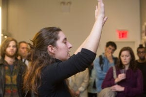 Woman performs in gallery space as people watch