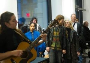Woman plays guitar in gallery space as gallery goers watch