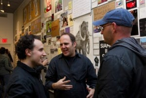 Three men converse while in gallery space