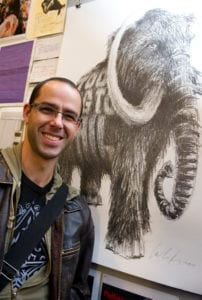 Man poses next to a black and white sketch of an Elephant.
