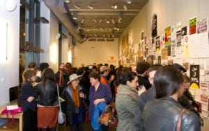 Gallery goers occupying the gallery space and viewing the various art works