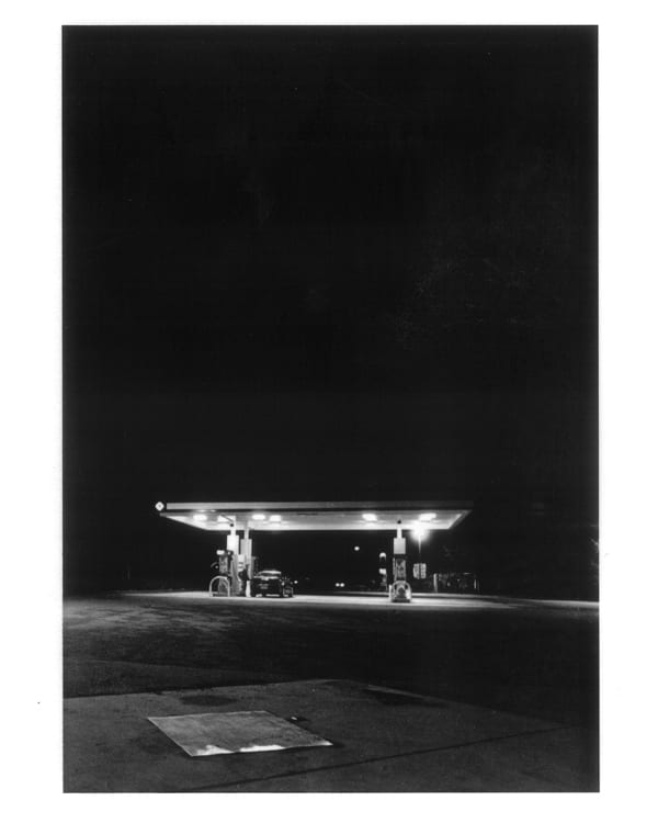 A black & white photograph of a gas station