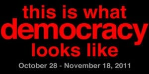 """Exhibition graphic: text in red font stating """"this is what democracy looks like"""""""