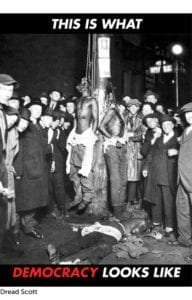 """Black and White image of a lynching. Two black men hung from their necks while a gang of white men watch and pose near them. Text with white and red font says """" This Is What Democracy Looks Like"""""""