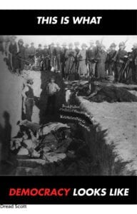 """Old black and white film print of various white soldiers watching a burial of war victims or enslaved black peoples. Text in red and white font says """" This is What Democracy Looks Like"""""""