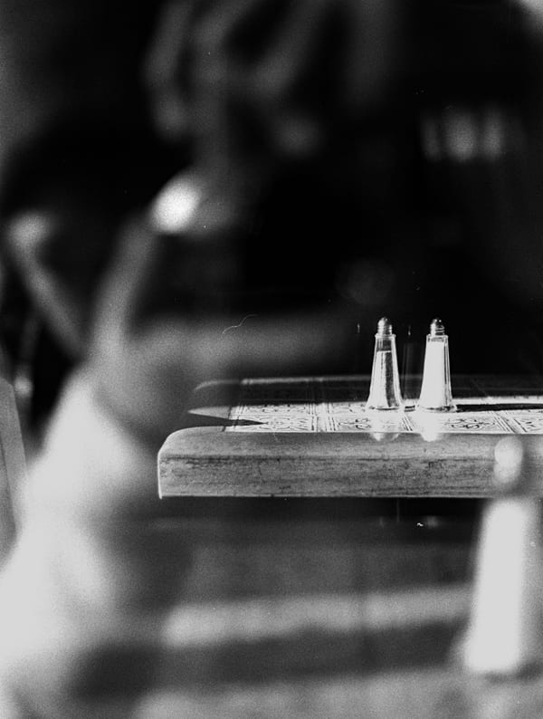 Black & white focused shot of salt and pepper shakers on a table.