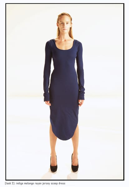 A model dressed in a blue midi dress with a curved hem at the bottom.
