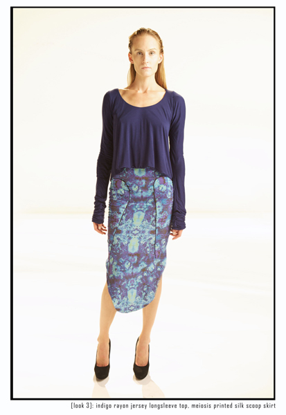 A model dressed in a flared blue top and purple and blue curved hem midi skirt.