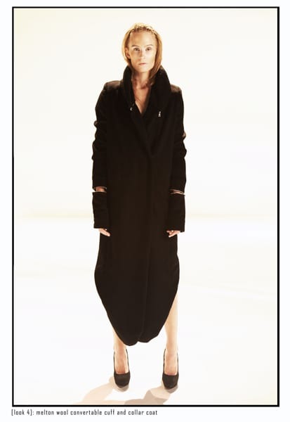 A model dressed in a black baggy curved hem midi dress.