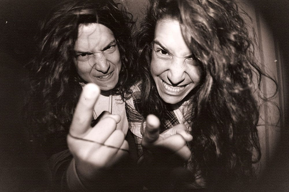 Two young men with long hair pointing a finger each at the camera in an expression of amusing rage