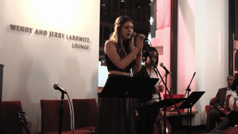Two girls singing on mics in the Jerry Labowitz lounge