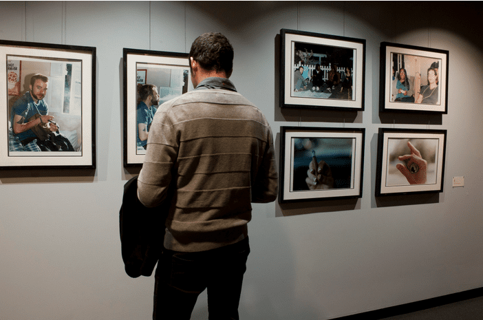 A man looking at the framed photos