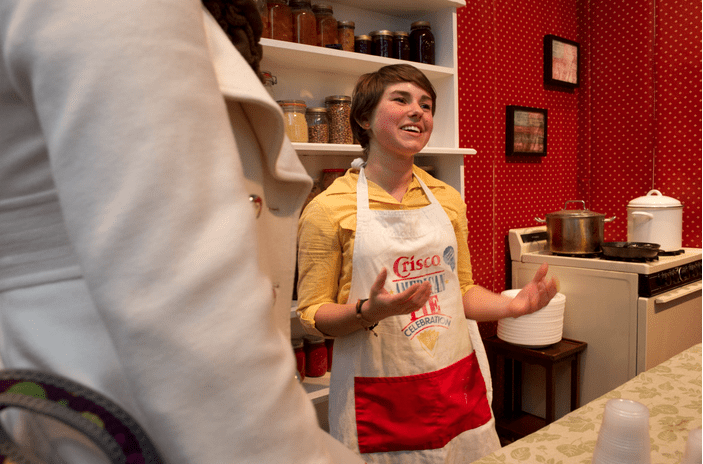 A female wearing an apron talking