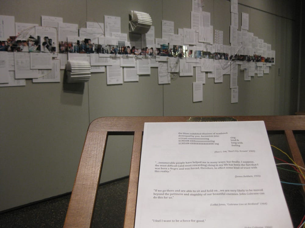 A document placed on a wooden pedestal and a large number of papers and notebooks pinned to the wall in the background.