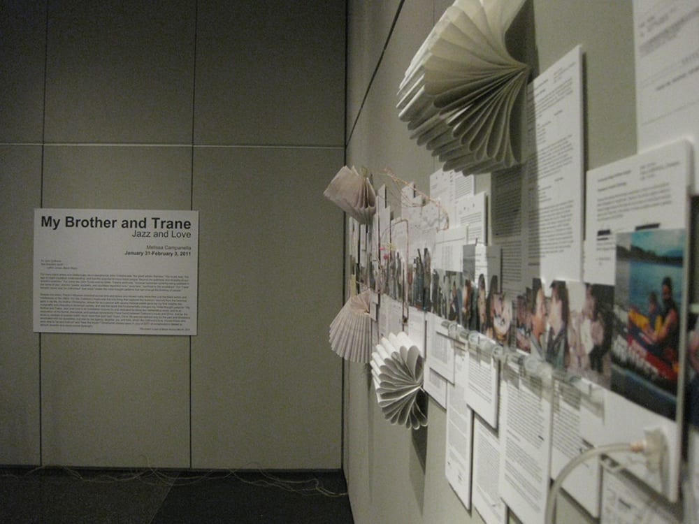 "A poster reading ""My brother and Trane"" and the wall with pages, notebooks and pictures on the side."