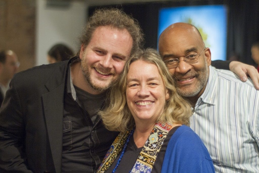 Portrait of three people (from left to right); Man, Woman, and another Man. All are smiling and embracing each other