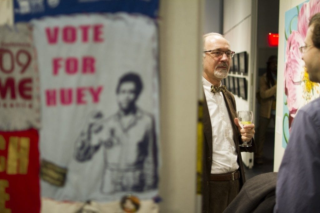 "Two men talking in gallery space. Gallery wall depicted on the left side, poster (not in focused) says ""Vote For Huey"" in pink font with a graphic of Huey Newton posing with a fist."