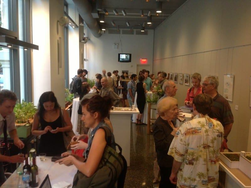 People looking at the exhibits and talking among groups in the gallery space