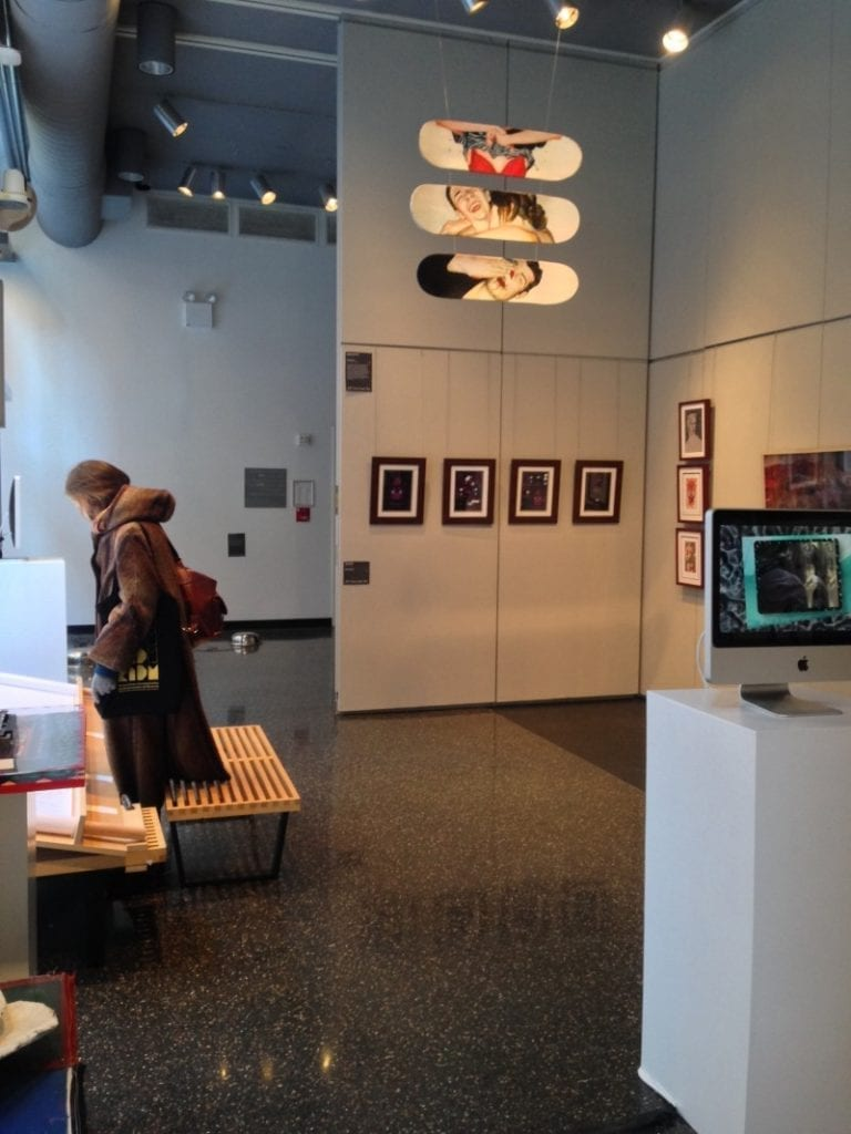 Gallery space. Woman analyzes work.