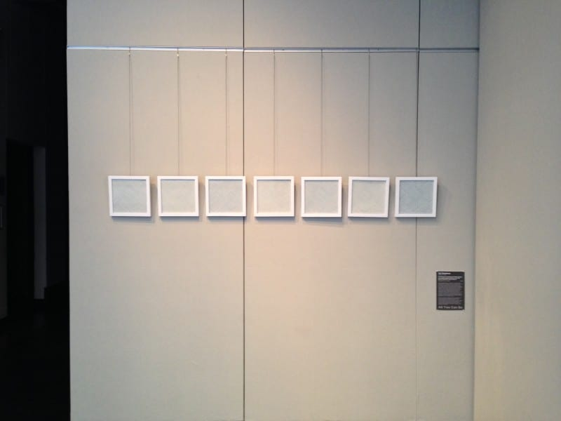 Gallery wall: 7 white frames with no images and an artist statement