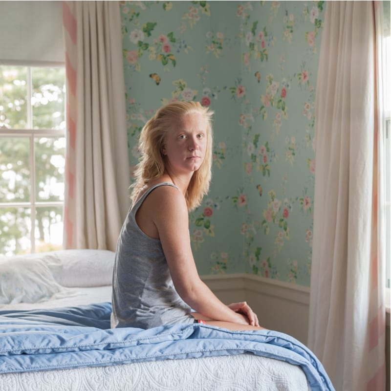 Portrait of young white woman in bedroom.