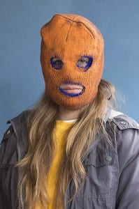 Portrait of young woman in orange ski mask. Female appears to be white and has long shabby blonde hair. She wears a grey coat with a yellow sweater and white T-shirt.