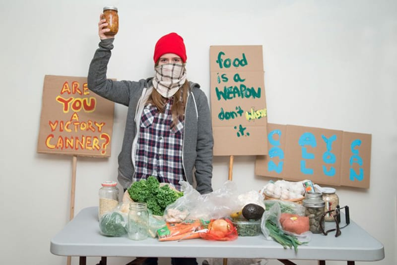Studio portrait of woman wearing red beanie, stripped scarf around her mouth, plaid shirt and grey hoodie, holding a mason jar full of food, while standing in front of protesting signs and near a table of various vegetables and cans.