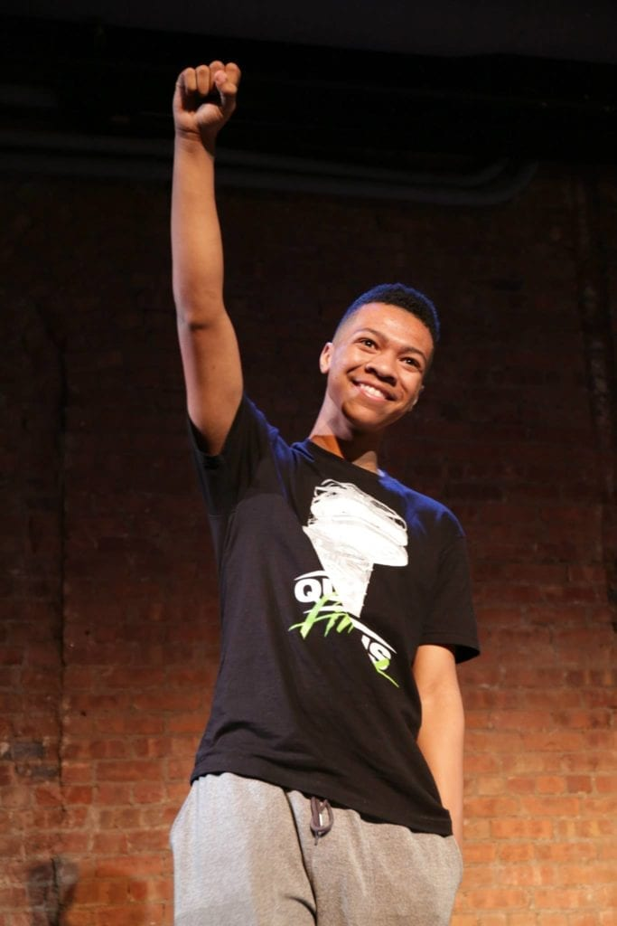 Portrait of young black man holding up his left fist in a theater.