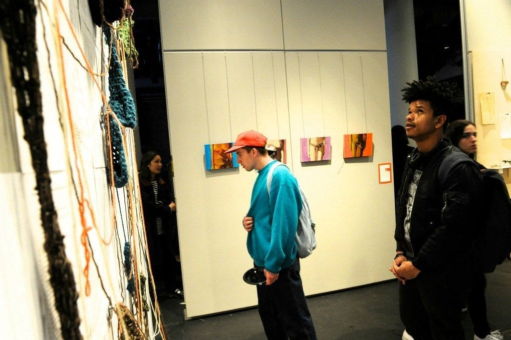 Two young men gaze at artwork in gallery space