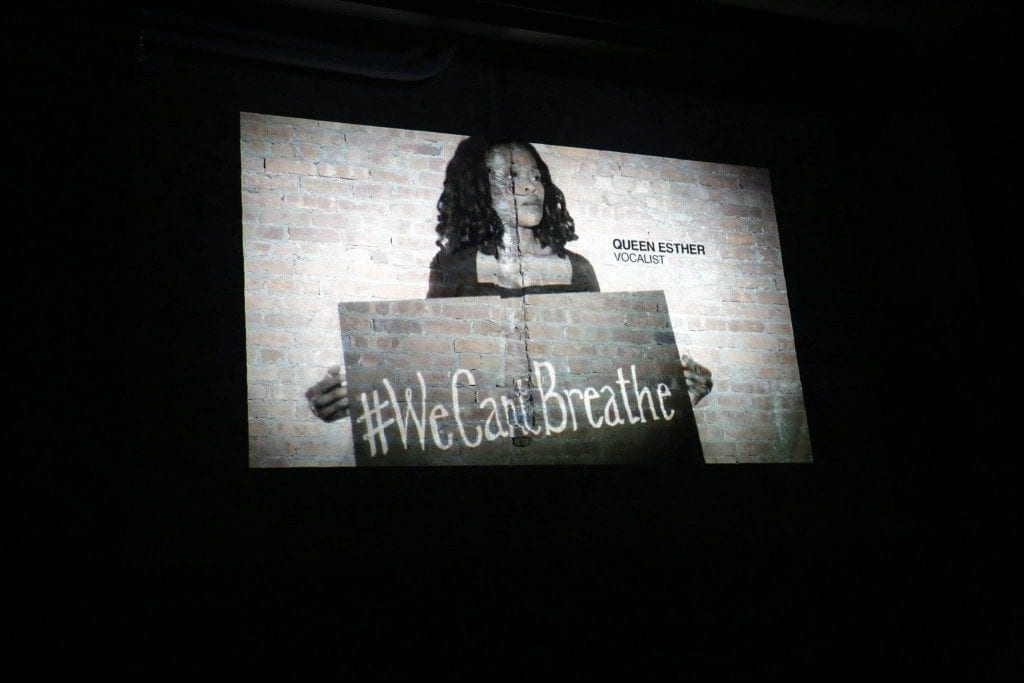 "Projected black & white image of black woman holding sign stating ""#WeCan'tBreathe"""