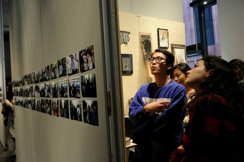 Students gazing at artwork on wall opposite from camera's perspective. Wall in view has various prints displayed on wall.