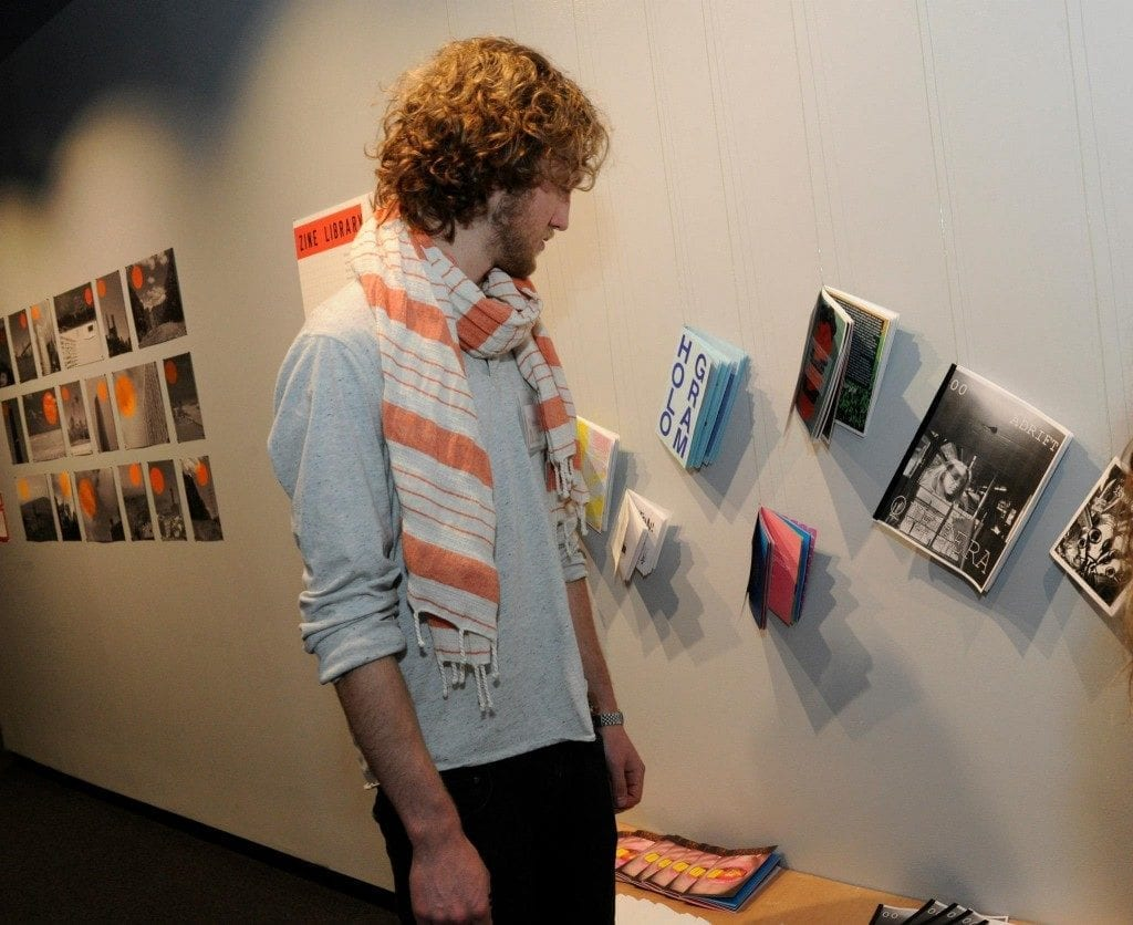 Young white man gazes at artwork on wall which is various zines pined to the wall.