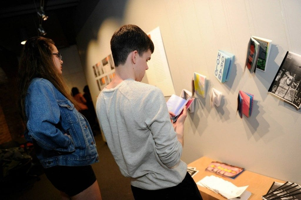 Two students, one male and one female, analyze zine artwork on wall.