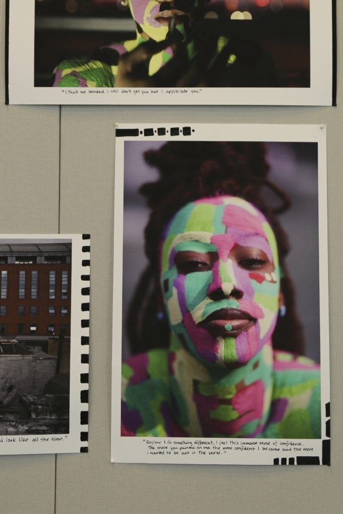 A young black woman with her face painted with pink and green