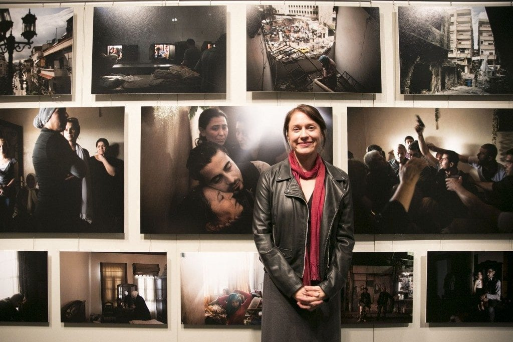 Andrea Bruce stands in front of art pieces