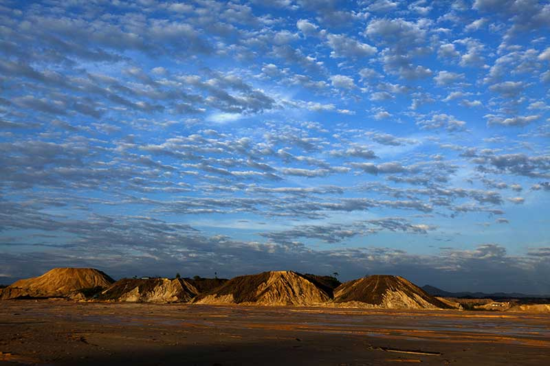 A scenic portrait of sand mountains and blue sky abundant with white clouds