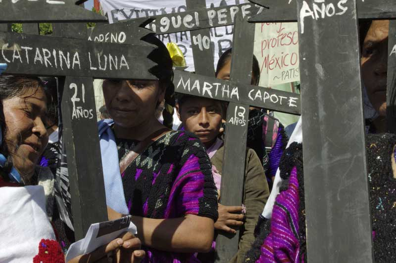 "A photo of women holding crosses bearing names of people killed or injured in Acteal massacre. ""Martha Capote"""