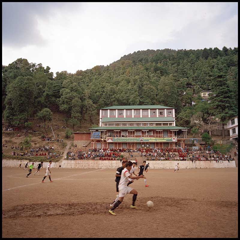 Children playing football in front of what seems like a school built in the style of a buddhist monastery.