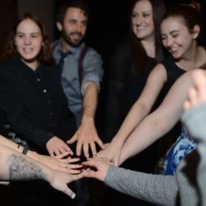 Eight people putting their hands together in a circle.