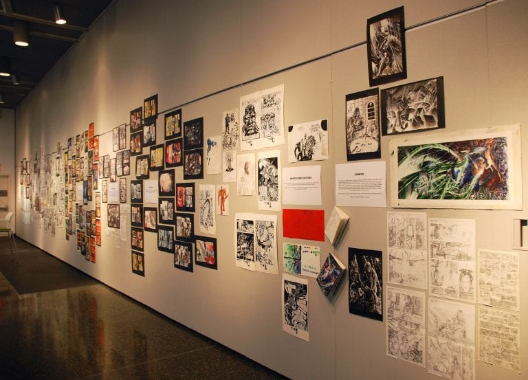 Gallery Space: Various comic illustrations in color and black & white on walls of gallery.