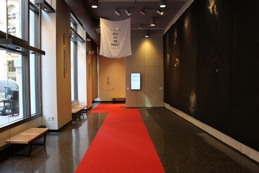 """Gallery space with red carpet and flag with the words """" Why Do We Fail?"""""""