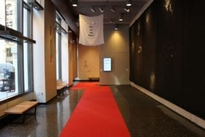 "Gallery space with red carpet and flag with the words "" Why Do We Fail?"""