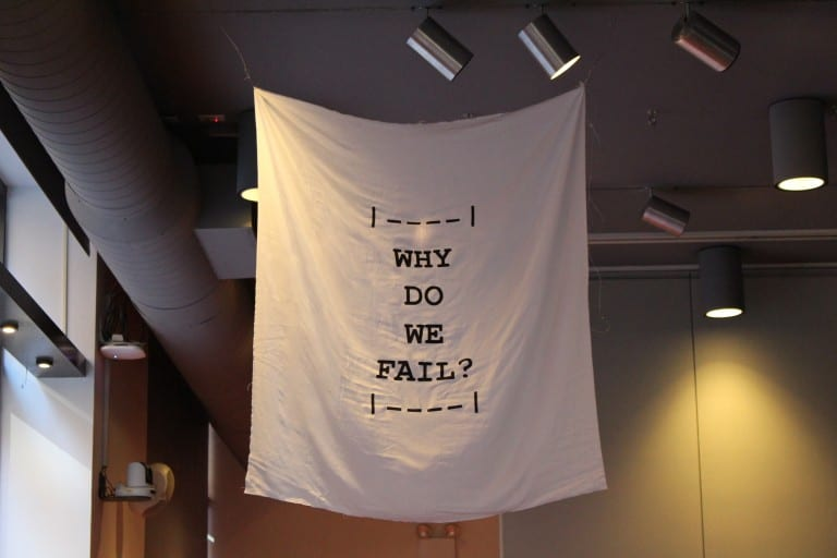 """Flag hanging from ceiling of gallery space with the text """"Why Do We Fail?"""""""