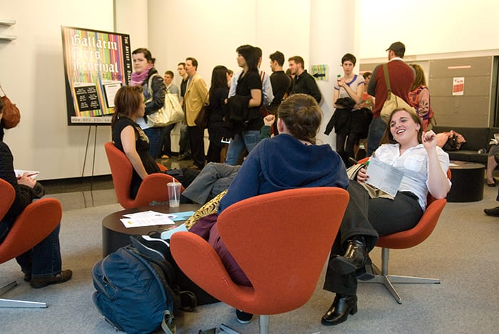 People sitting in the Gallatin lounge engaged in conversation after a festival event