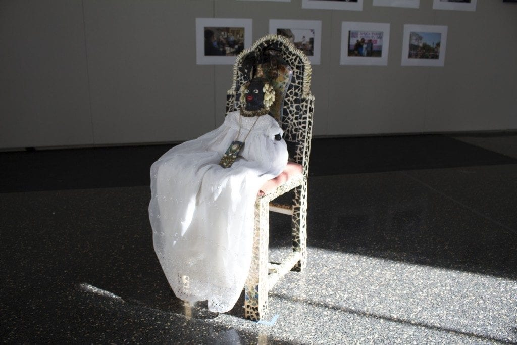 African doll on a chair placed in the gallery space