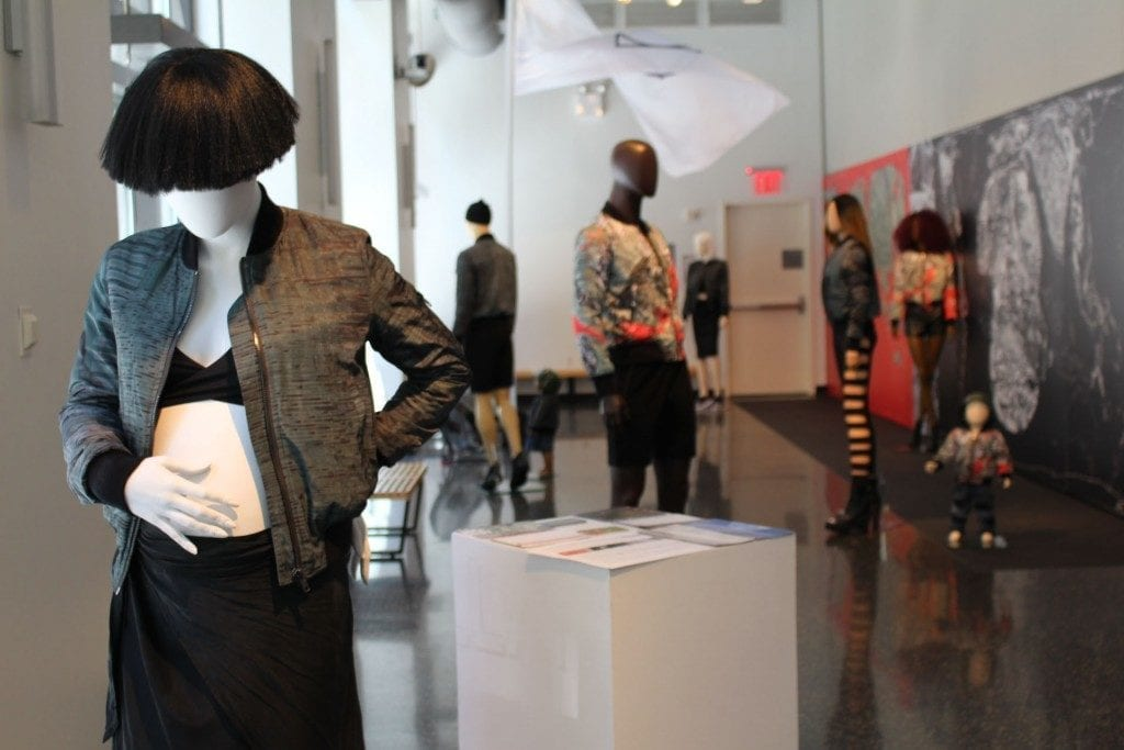 Gallery space: mannequins exhibiting clothing line.