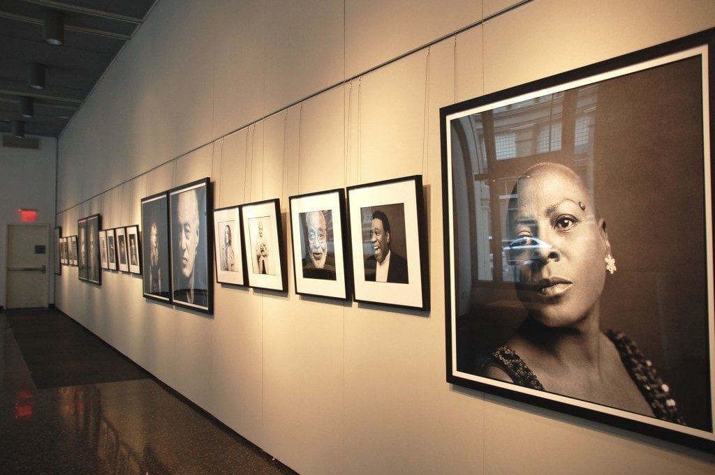 Gallery space with portraits on wall.