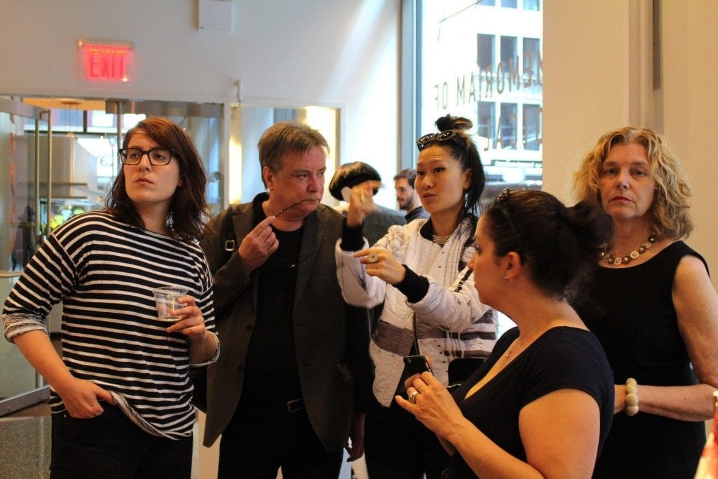 Multiple people talking in gallery space including artist.